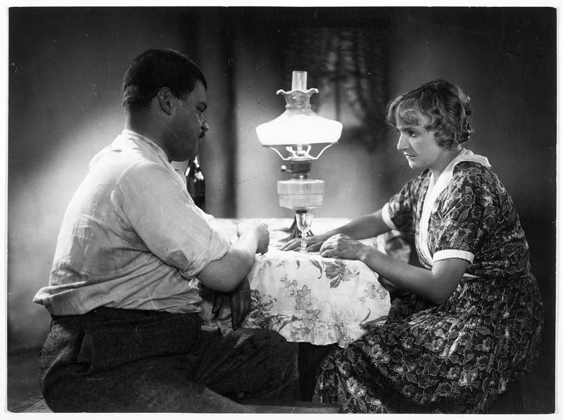 Un homme (F. Kortner) et une femme (M. Delschaft) buvant un verre ensemble
