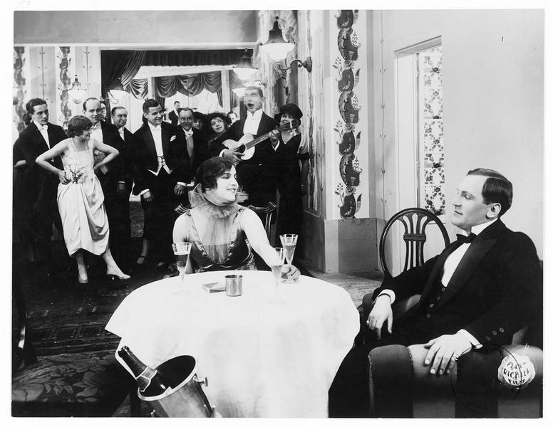 Un homme (F. Achterberg) et une femme (E. Richter) buvant du Champagne