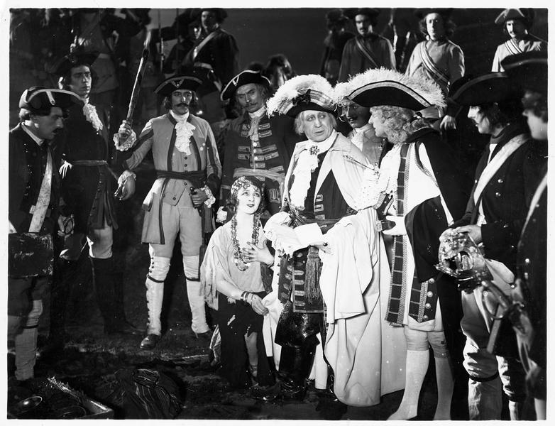 Une femme à genou devant une assemblée d'hommes