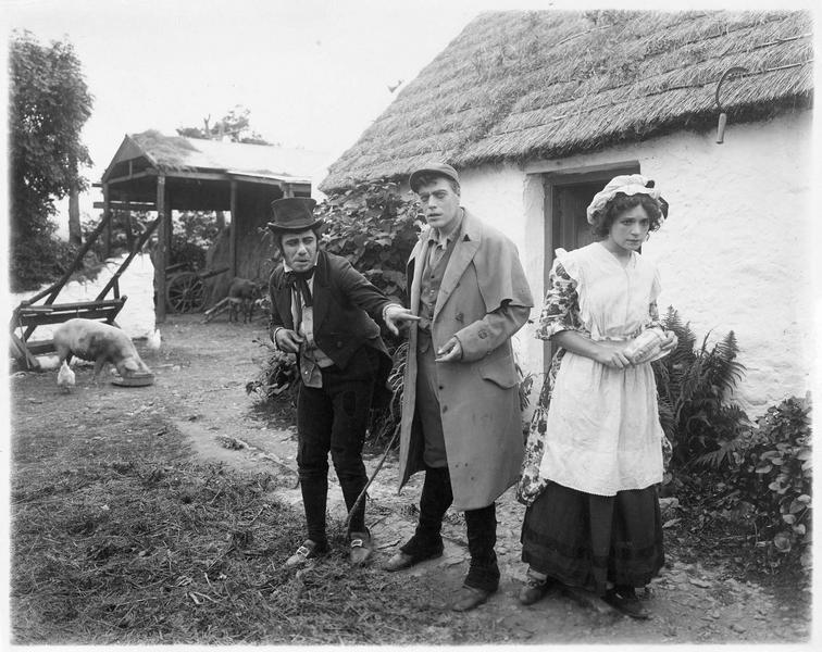 Une jeune femme et deux hommes devant une maison au toit de chaume