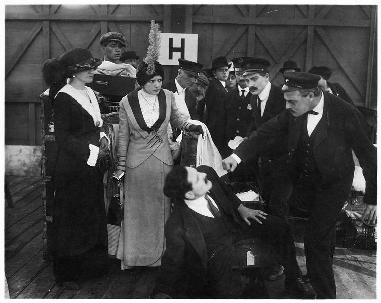 Un homme assénant un coup de poing à sa victime sous le regard d'une femme élégante