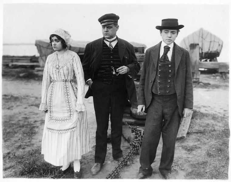 Jeanne Desfree (V. Grant), un marin (A. Randolf) et Victor Morenne (W. Whiteside) à côté d'un pasteur (R. Carleton)