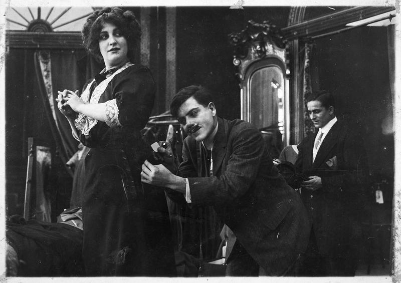 Un homme (H. Myers) glissant un petit papier dans la poche de la robe d'une femme (O. Handworth)