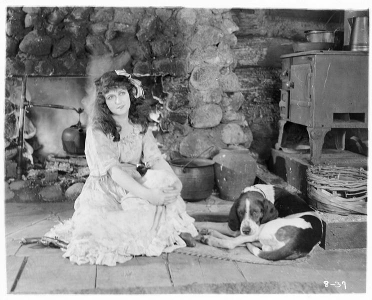 Cynthy Quimby (P. Hyland) assise devant la cheminée avec le chien