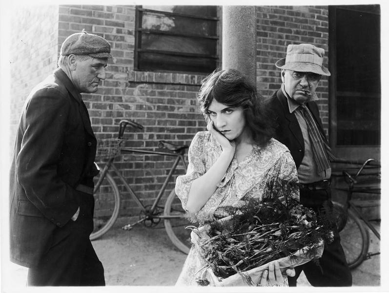 Jeune femme (F. Lawrence) portant une cagette de fleurs