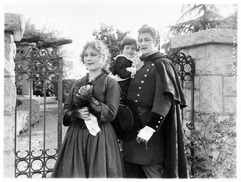 Helen Reed (L. Lovely) et Jerry Brennon (A. Holubar) tenant un enfant dans ses bras