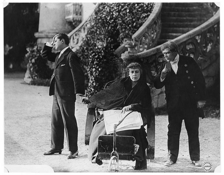 Une femme (G. Dermoz) sur une chaise roulante entourée de deux hommes