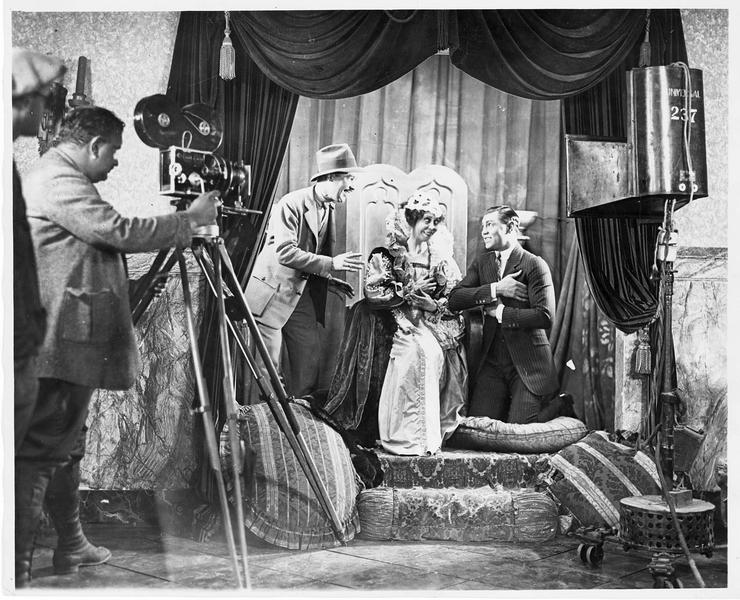 Jack Dempsey répétant une scène d'amour, tandis que le réalisateur Jess Robbins lui montre comment faire l'amour à une reine