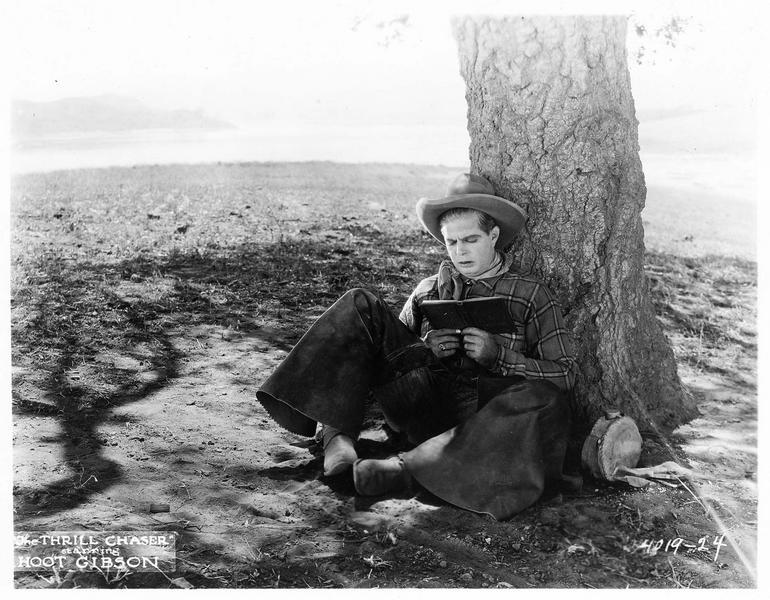 Omar K. Jenkins (H. Gibson) lisant un livre, assis sous un arbre