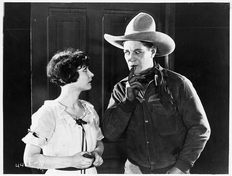 Un cow-boy (H. Gibson) faisant signe à une femme de ne pas faire de bruit