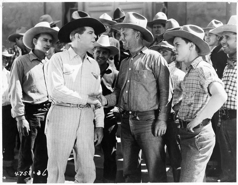 Dennis O'Hara (H. Gibson) échangeant une poignée de main avec un autre cow-boy