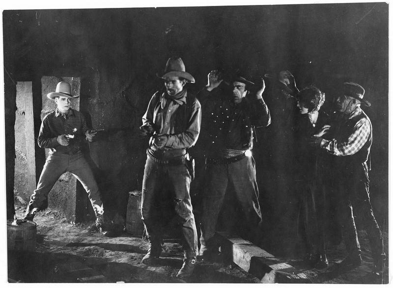 Un homme (H. Gibson) mettant en joue un groupe de personnes