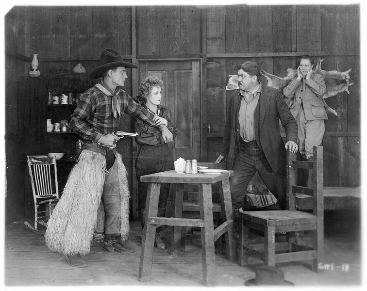 Chick Crandall (B. Jones) menaçant un homme avec son revolver