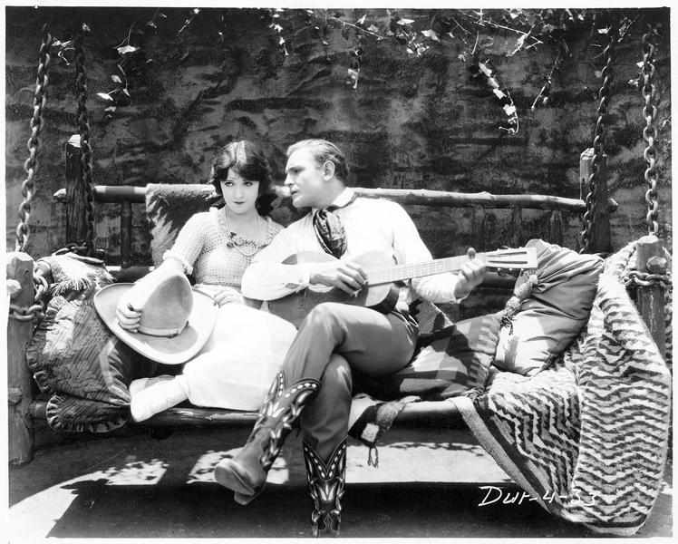Jim Blake (B. Jones) jouant de la guitare auprès de Doris Lane (H. Ferguson)