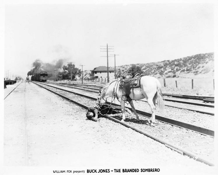 Starr Hallett (B. Jones) tombé sur la voie de chemin de fer, alors qu'un train arrive au loin