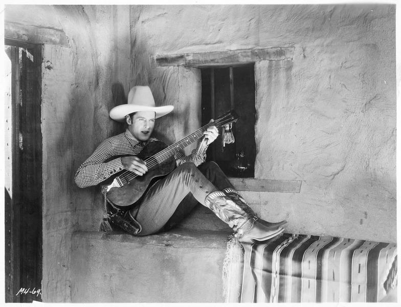 Moment de détente pendant le tournage : Ken Maynard jouant un vieil air espagnol à la guitare