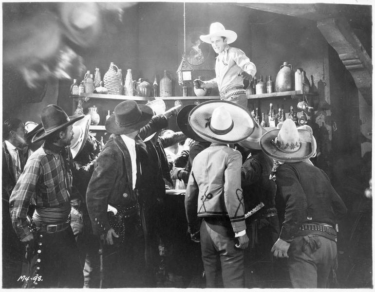Bob Bishop (K. Maynard) debout sur le comptoir d'un saloon