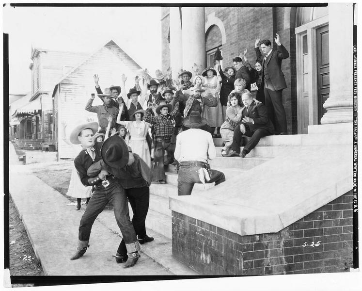 Johnny Bowers (P. Morrison) neutralisant un homme, tandis que son compagnon tient en joue un groupe d'hommes et de femmes à la sortie du temple