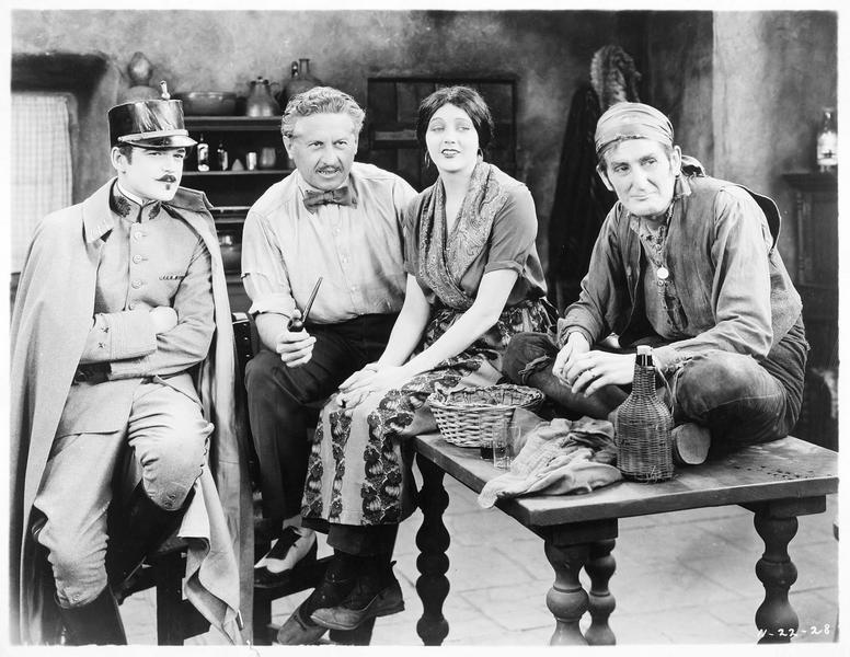 Guerita (B. La Marr) entourée de trois hommes dans cuisine