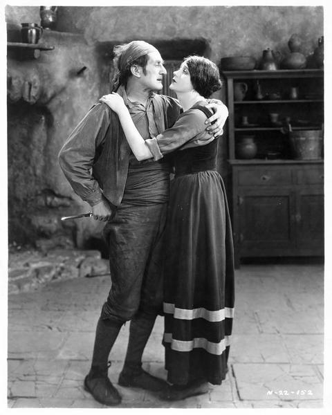 Guerita (B. La Marr) dans les bras d'un homme qui cache un couteau dans son dos