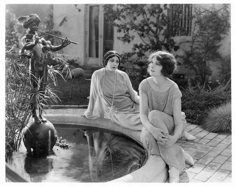 Deux jeunes femmes assises au bord d'un bassin