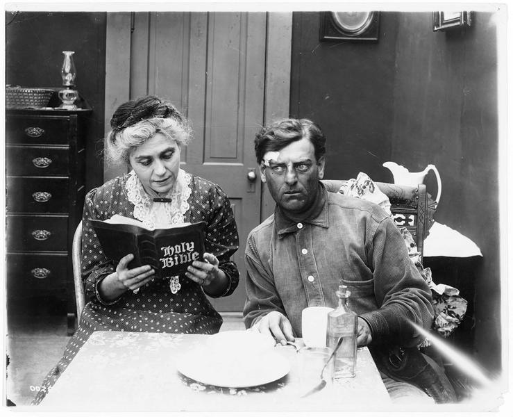Un homme (G. M. Anderson) écoutant une femme qui lit la Bible