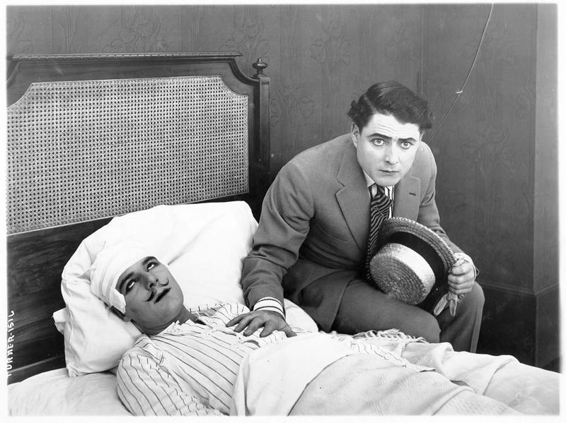 Un homme (J. Kerrigan) posant sa main sur le coeur d'un malade alité