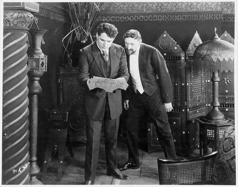 Deux hommes déchiffrant un parchemin