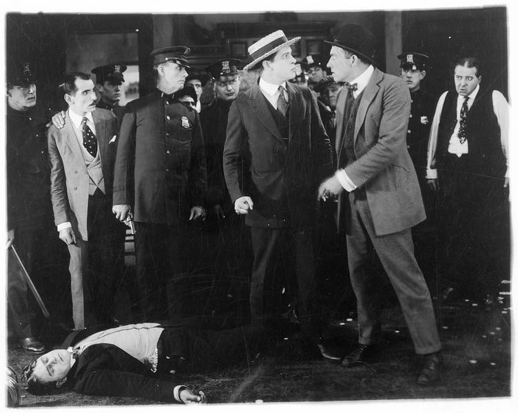 Deux hommes sur le point de se battre devant des policiers et un homme gisant au sol
