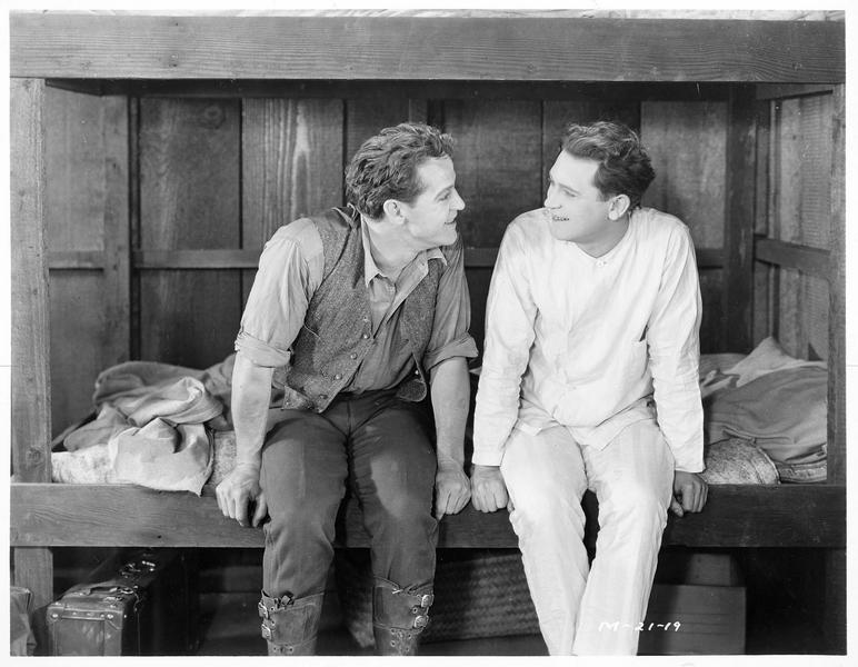 Peter Brent (W. Russell) échangeant un regard complice avec un ami