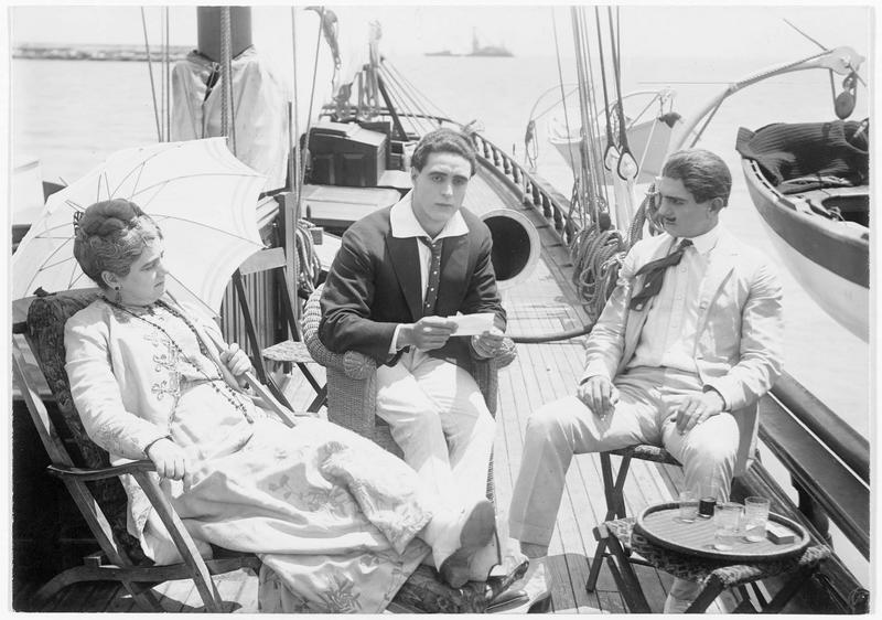 Hawksford (G. Walsh) et Bartollomeo Boceni (F. MacDonald) assis sur le pont d'un bateau en compagnie d'une femme