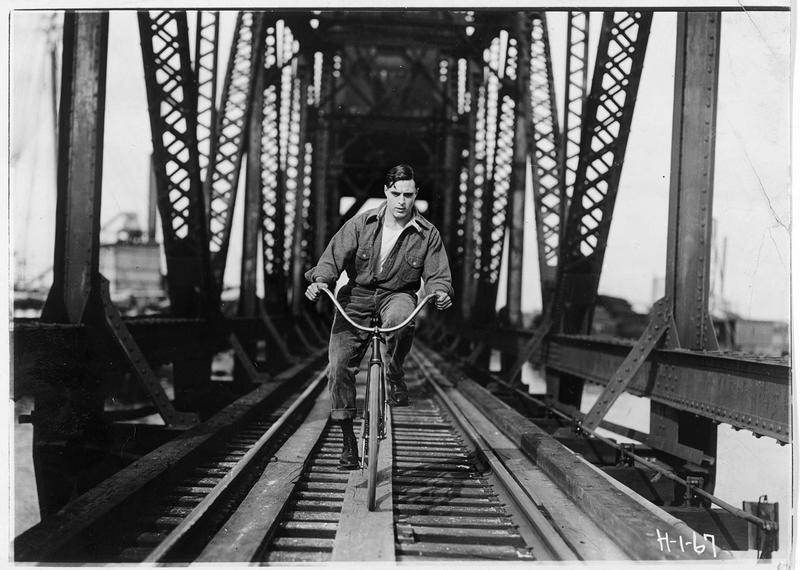 Shark Rawley (G. Walsh) roulant à bicyclette sur le pont d'une voie ferrée