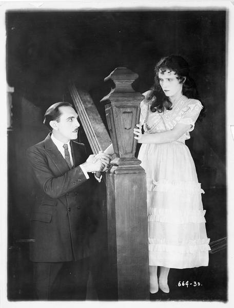 Un homme tenant fermement la main de Pegeen O'Barry (P. Starke)