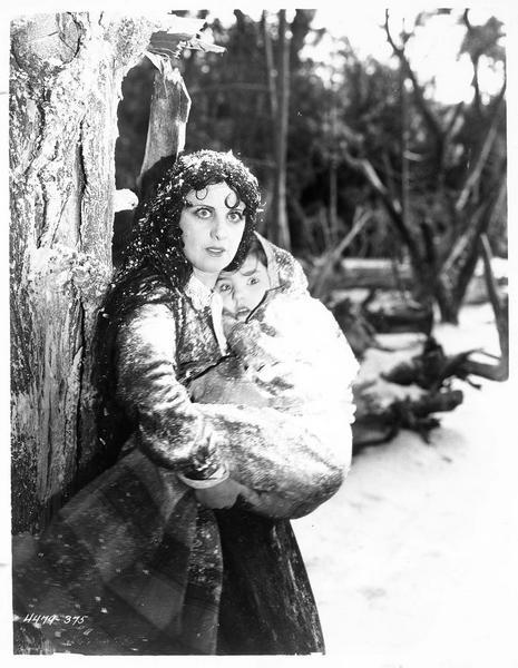 Eliza (M. Fisher) dans la neige avec une fillette dans les bras