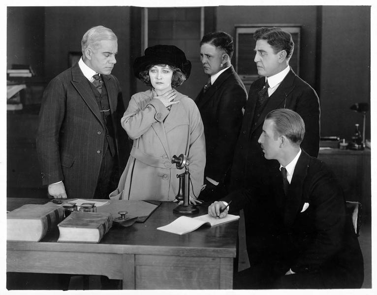 Cassy Cara (P. Frederick), le regard vide, entourée de quatre hommes qui la regardent