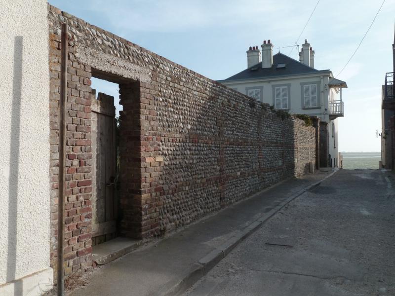 Mur de clôture. Opus mixtum de briques et de galets en structure croisée.