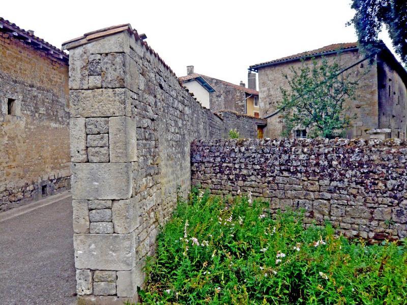 Mur de clôture. Tête de mur réalisée avec des boutisses, des panneresses et des pierres taillées pour le remplissage.