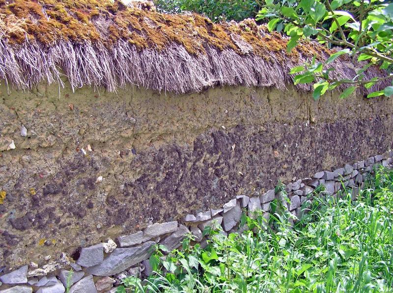 Mur de clôture. Chaperon en chaume sur un mur de terre crue.