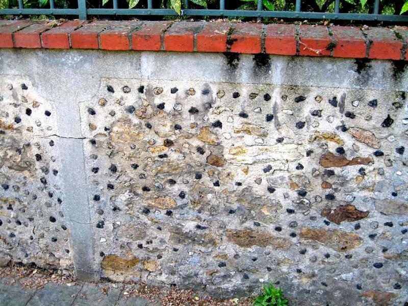 Mur de clôture. Enduit avec pointes de silex noir.