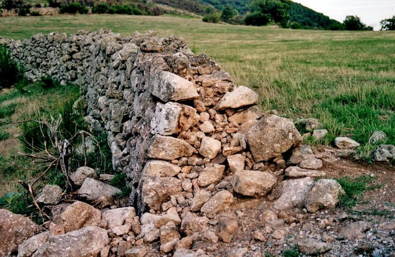 Mur de clôture. Mur à double parement avec remplissage en cailloutis.