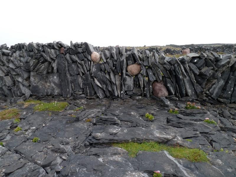 Mur de clôture. Plaques de calcaire et galets de granit.