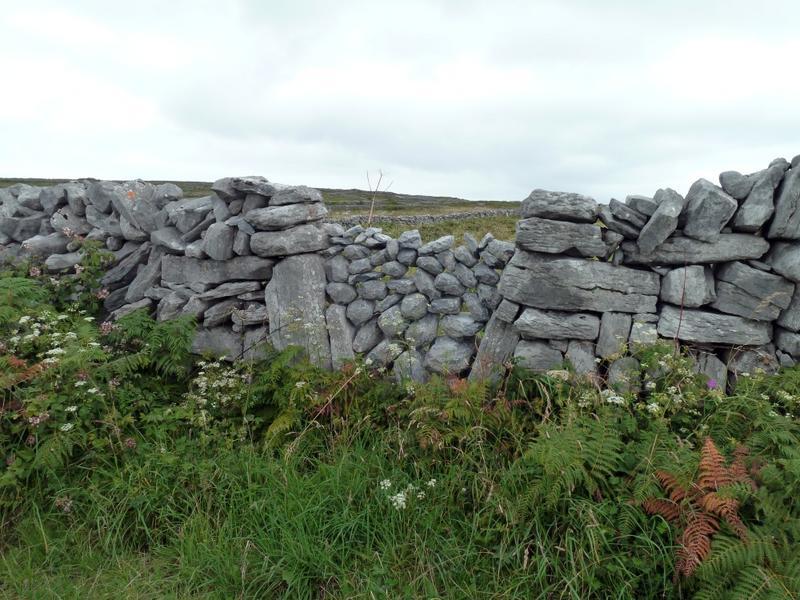 Mur de clôture. Ouverture constituée d'un entassement de pierres entre deux longues pierres verticales.