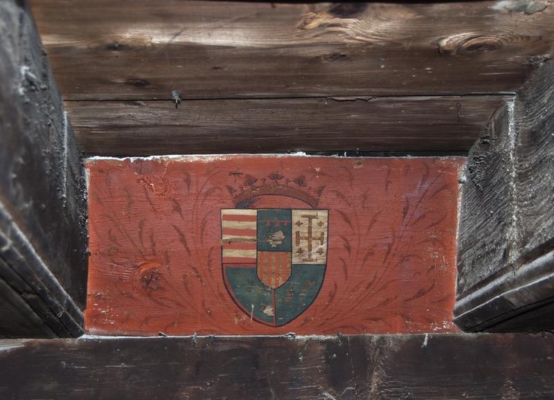 Closoir portant une peinture d'une demi-ellipse avec des armoiries surmontée d'une couronne.