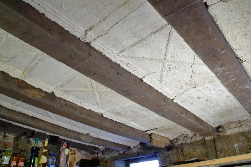 Plafond à entrevous en plâtre décoré. Vue sur trois travées.