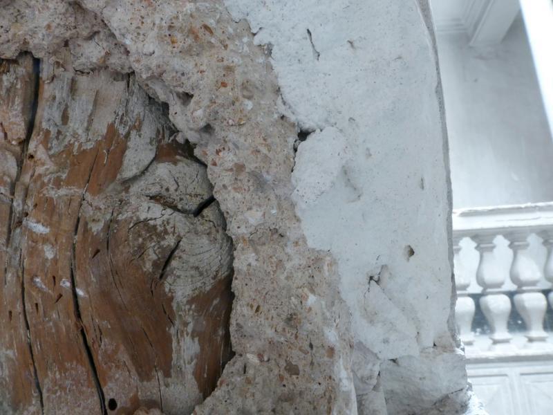 Épaufrure sur la dixième colonne, découvrant un bois rond, le mortier de plâtre, le plâtre et l'enduit