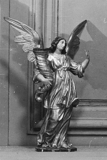 Chandeliers (2) : paire d'anges en bois sculpté, peint et doré, portant chacun une corne surmontée d'un pique-cierge (trois quart)