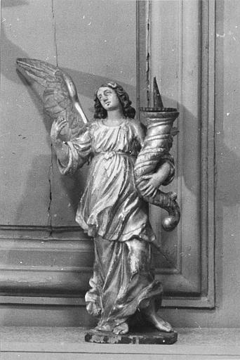 Chandeliers (2) : paire d'anges en bois sculpté, peint et doré, portant chacun une corne surmontée d'un pique-cierge (face)