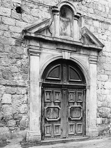 Porte en bois cintrée à décor de moulures formant des motifs géométriques, surmontée d'une niche