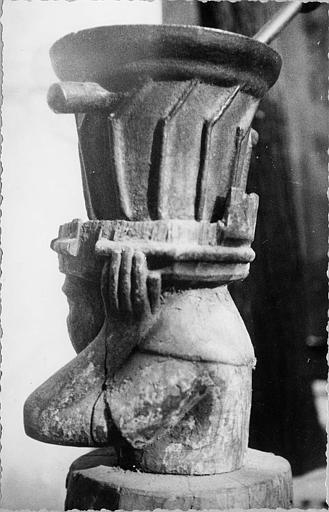 Mortier, billot : mortier en fonte à poignées, billot en bois sculpté d'un buste de personnage (dos)