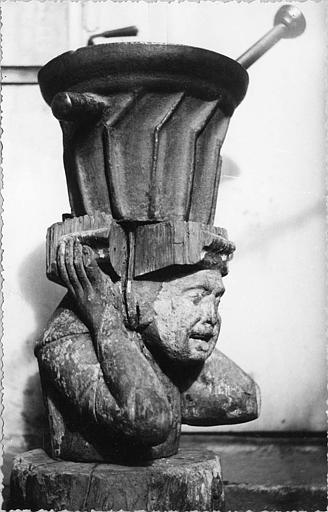 Mortier, billot : mortier en fonte à poignées, billot en bois sculpté d'un buste de personnage (trois quart)